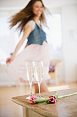 Champagne flutes on table, woman dancing in background