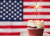 Studio shot of sparkler atop cupcake, american flag in background