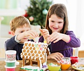 Girl (8-9) and boy (6-7) preparing gingerbread decorations