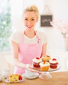 Smiling young woman in apron holding cake stand
