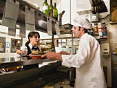 Waitress gesturing to chef in restaurant kitchen