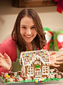 Portrait of young woman with gingerbread house in kitchen