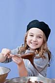 Mädchen mit einem Löffel Schokoladenteig