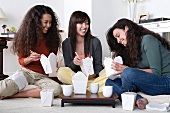 Three female friends eating take out food at home