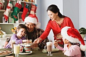 Family with two daughters (10-11) enjoying christmas meal
