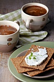 Crispbread topped with cream cheese, with two cups of coffee