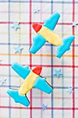 Two airplane cookies on a plaid cloth with blue stars