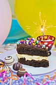 A piece of chocolate cake with colorful sprinkles and candy decorations for a party. Sparkler. Confections
