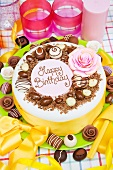 Birthday cake with chocolate candies, roses and a yellow bow