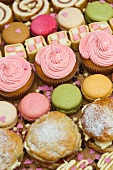 Rows of cupcakes, scones, macarons, Swiss rolls and pieces of mini Battenburg cake