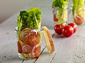 Romaine lettuce with red onion and tomatoes in glasses
