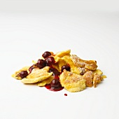 Kaiserschmarren (sweet cut up pancakes) with cherry compote in front of white background