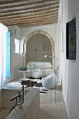 Bad Ensuite mit Natursteinwanne; Schnurvorhang als Abgrenzung zu Sitzplatz mit Designermöbeln und Bett in orientalischem Alkoven