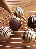 Decorating pralines with chocolate