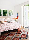 Doppelbett mit Betttisch in sonnigem Zimmer mit offener Falttür zur Gartenterrasse; am Boden ein Webteppich im Ethnolook