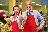 Germany, Cologne, Man and woman in supermarket showing thumbs up, smiling, portrait