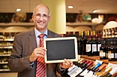 Germany, Cologne, Mature man holding blackboard in supermarket, smiling
