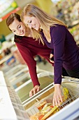 Germany, Cologne, Young women at freezer in supermarket