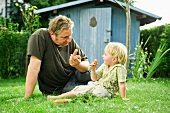 Germany, Bavaria, Father and son eating carrots