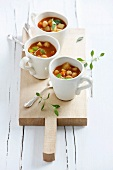 Cups of potato chickpea soup on chopping board