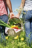 Germany, Cologne, Young couple with picnic basket in meadow