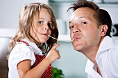 Germany, Daughter eating noodles with father in kitchen
