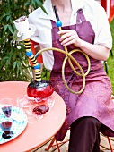 Person sitting on terrace with a hookah pipe