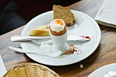 A soft egg in an eggcup and bread on a plate