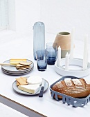 A table laid with bread, cheese, candles, vases and glasses