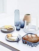 Gedeckter Tisch mit Brot, Käse, Kerzen, Vasen und Gläsern