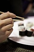 A hand reaching for a piece of sushi using chopsticks