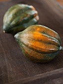 Two Whole Acorn Squash on a Wooden Tray