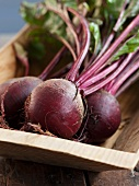 Whole Beets with Beet Greens in a Wooden Tray