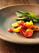Sliced Red and Yellow Cherry Tomatoes with Fresh Basil in a Ceramic Plate