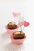 Miniature chocolate cakes topped with heart-shaped decorations