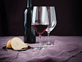 A Glass of Bordeaux Wine with a Halved Pear; Empty Wine Glass and Wine Bottle