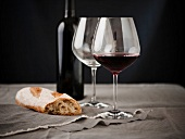 A Glass of Burgundy Wine with a Piece of Bread; Empty Wine Glass; Wine Bottle