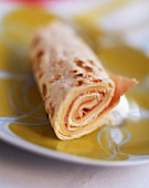 A rolled crêpe filled with ham and cheese