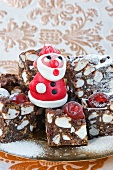 a model in red marzipan of father Christmas standing on squares of rocky -road cakes for Christmas with gold patterened paper