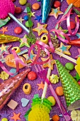 overview still life of various party decorations, party poppers sweets and straws for the party table on a purple glittery table
