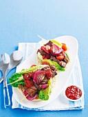 Marinierte Rindfleischspießchen mit Salat auf Grillbrot; dazu Tomatenchutney