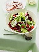 A bowl of mixed salad leaves and a plate of ham