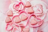 Rosa Schokoladenpralinen mit herzförmigen Ausstechformen auf einem pastellfarbenen Rosenmuster
