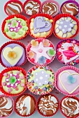 overview o of coloured cup cakes in red and pink plastic cake covers decorated with hearts, lips and sweets