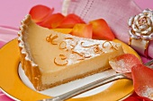 close up of a single serving of lemon pie slice on a yellow and gold ceramic plate with a pink table cloth and napkin with orange rose petal