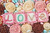 still life of four pink square iced cakes with letters on the top which spell the word love, surrounded by coloured cup cakes and sweets