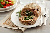 Meatloaf made from beef and stuffed with spinach and pine nuts