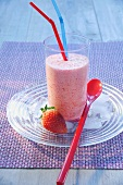 Strawberry milkshake in a glass with drinking straws