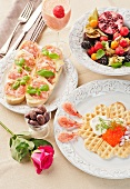Frühstück mit Kaviar-Waffel, belegten Broten, frischen Früchten und einem Erdbeer-Mango-Smoothie