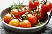 Tomatoes on the vine, seasoned and in the pan